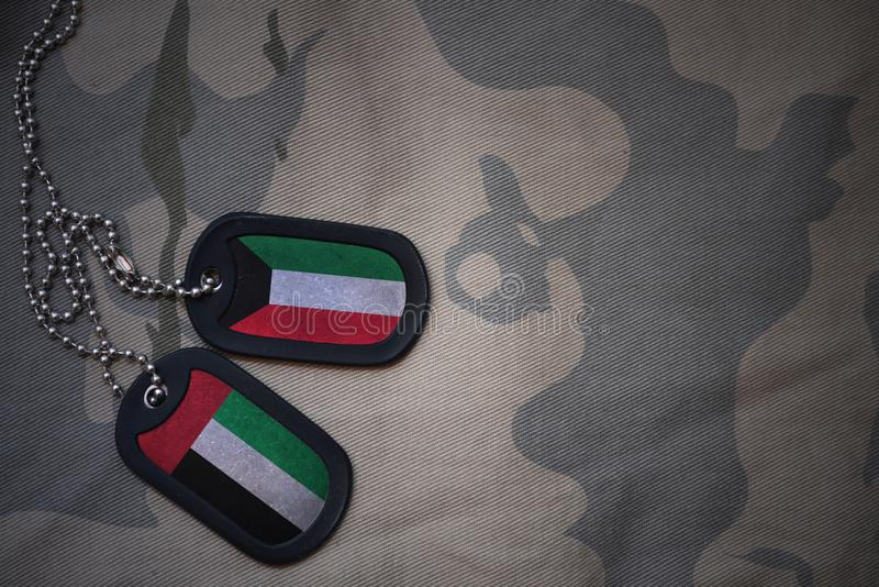 armémellanrum, hundetikett med flaggan av Kuwait och Förenade Arabemiraten på den kaki- texturbakgrunden arkivfoto