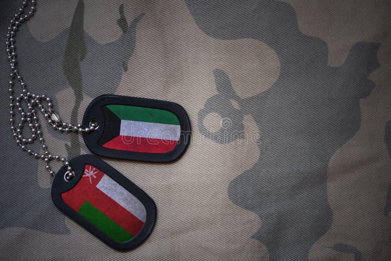 armémellanrum, hundetikett med flaggan av Kuwait och Oman på den kaki- texturbakgrunden arkivfoton
