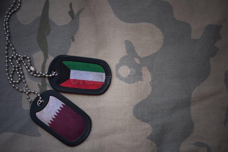armémellanrum, hundetikett med flaggan av Kuwait och Qatar på den kaki- texturbakgrunden arkivfoto