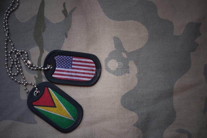 armémellanrum, hundetikett med flaggan av USA och guyana på den kaki- texturbakgrunden royaltyfria foton