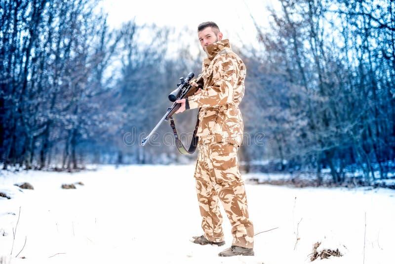 Arméprickskytt under militär operation genom att använda ett yrkesmässigt gevär på en kall vinterdag arkivfoto