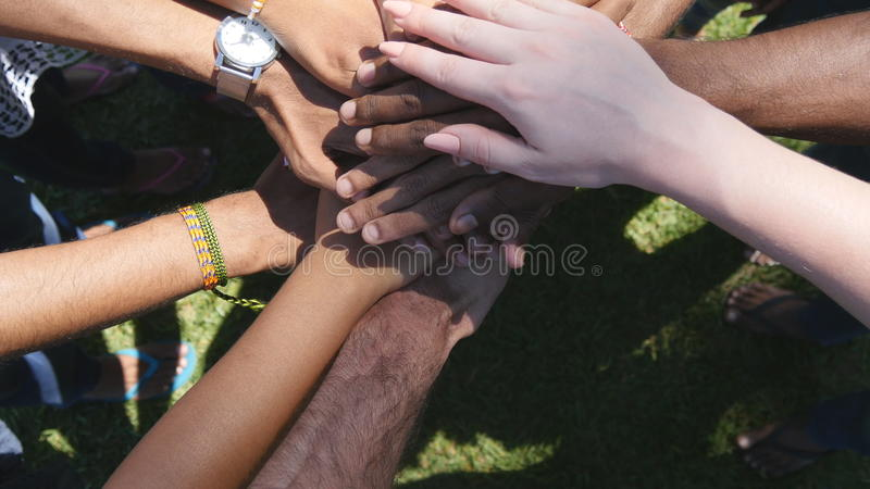 Arm of all races and colors stacked together one by one in unity and teamwork and then raised. Many multiracial hands royalty free stock images