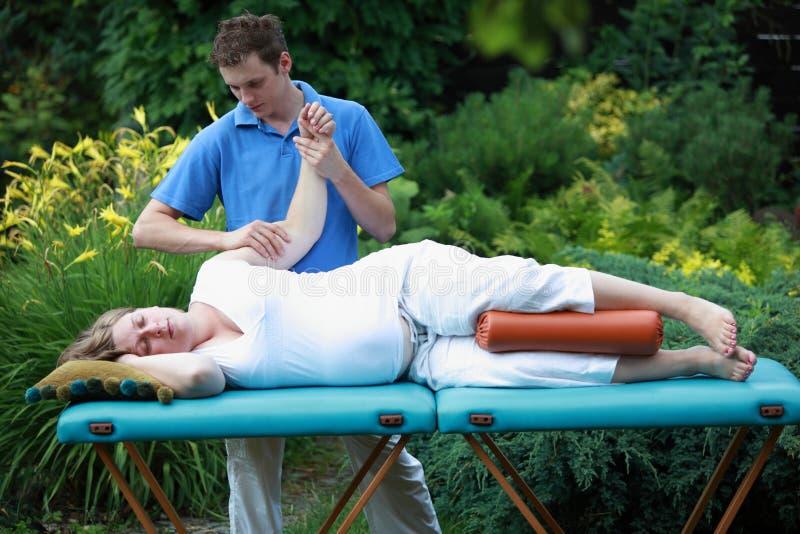 arm den fysiska gravida terapeutkvinnan för massagen royaltyfri fotografi