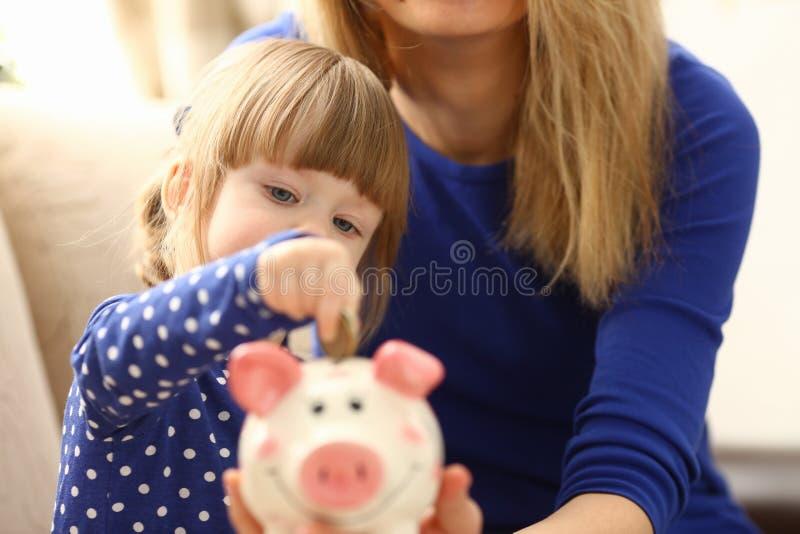 Arm des Kinderkleinen Mädchens, der Münzen in piggybank setzt stockbilder