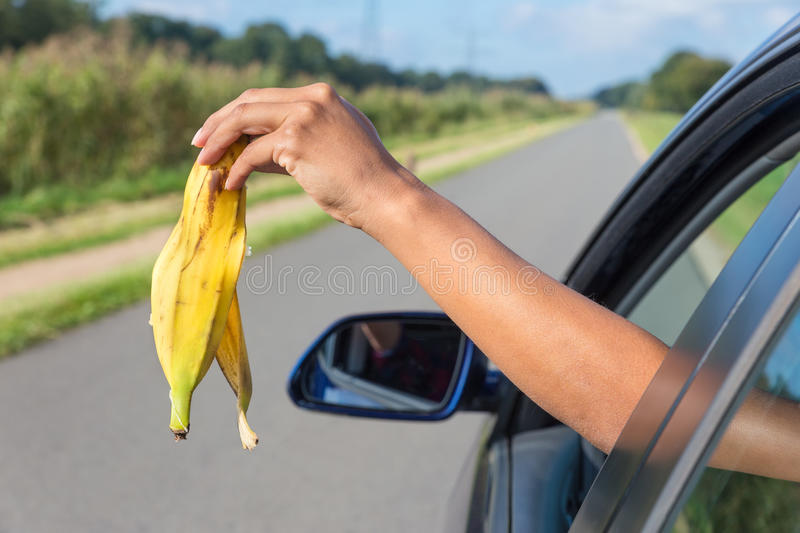 Arm dropping peel of banana out car window. Female arm throwing fruit waste out of car window royalty free stock photography