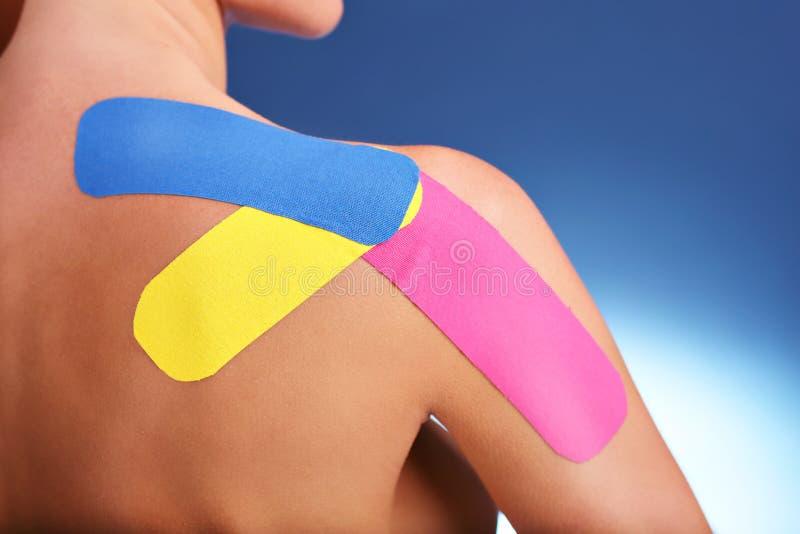 Arm för specialt physio band för bildvisning pålagd sårad över vit bakgrund royaltyfri bild