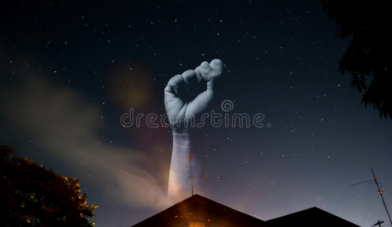 Arm fist showing at night sky. Body part. A wrist showing in the night sky with many stars. A symbol of strong. Night sky view, house roof, triangle, tree royalty free stock images