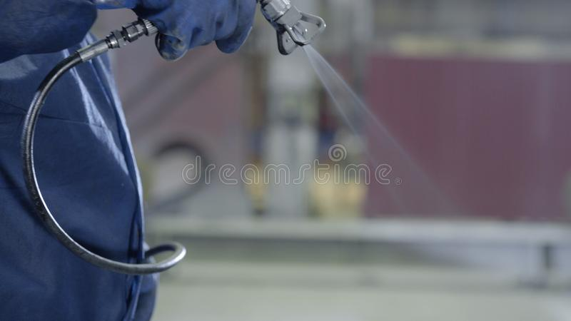 Arm hand holding industrial size spray gun used for industrial painting and coating. Male hand holding paint spray. Closeup stock photography