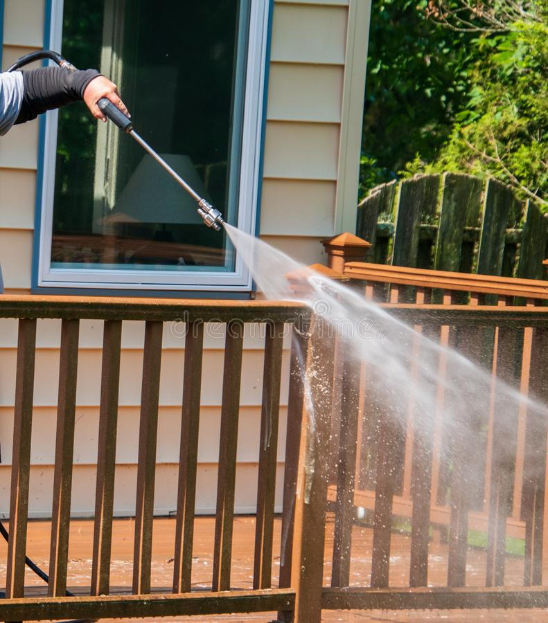 Arm holding a water pressure sprayer is seen spraying water on the brown wooden railing of a deck. Arm holding a water pressure sprayer is seen spraying water stock photos