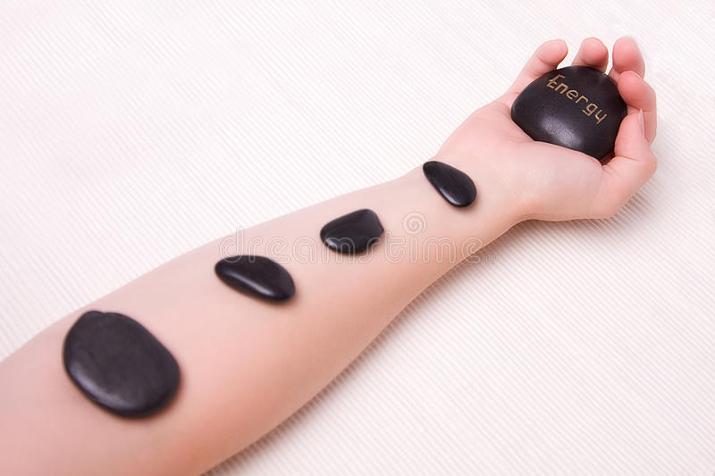 Arm with hot Stone Energy stock photography