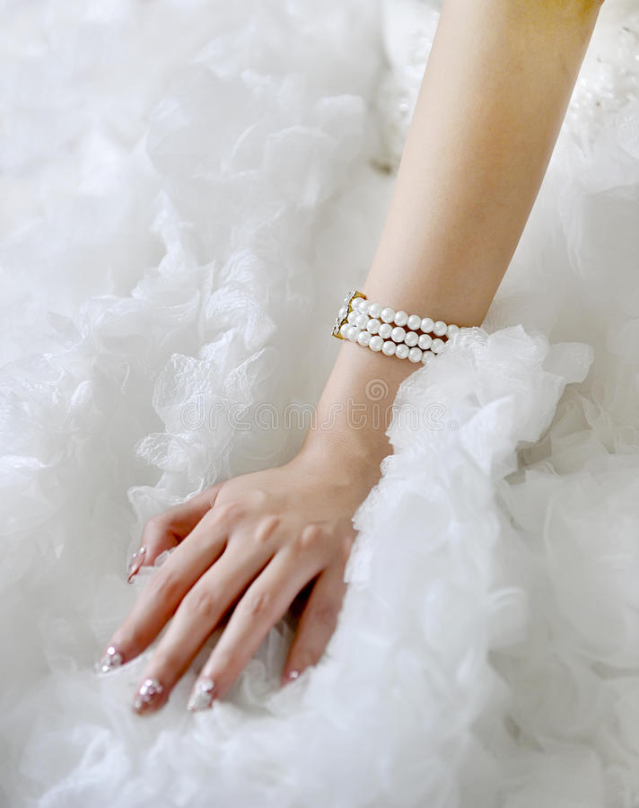 Arm jewelry. The bride beautiful arms and white wedding gown, reflected the newly married happiness。Arm jewelry, reflected the woman of showily stock photos