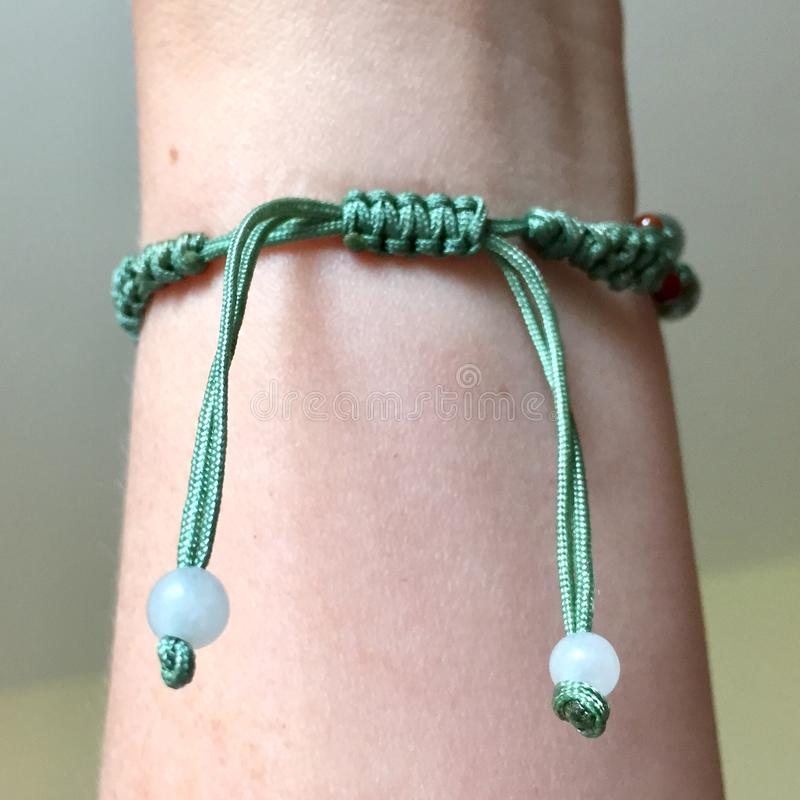 Arm with a knot of a bracelet stock photos
