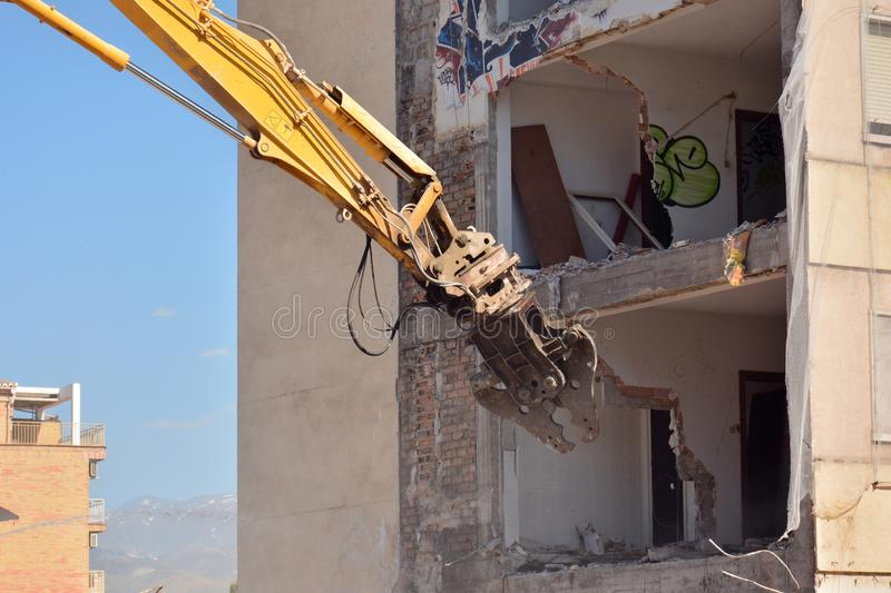 Arm of machine demolishing an apartment building. Large machine demolishing walls and pillars of an old residential building royalty free stock photography
