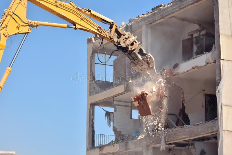 Arm of machine demolishing an apartment building. Large machine demolishing walls and pillars of an old residential building stock photos