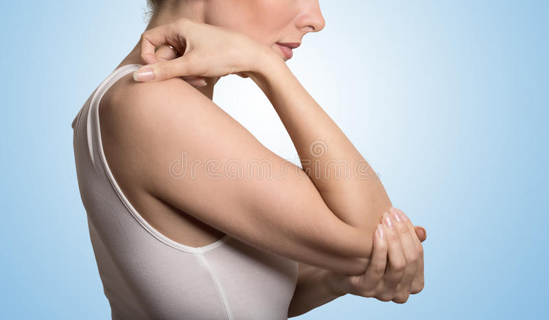 Arm pain and injury concept. Closeup side profile woman with painful elbow. Cropped image woman with joint inflammation. Female's elbow. Arm pain and injury stock image