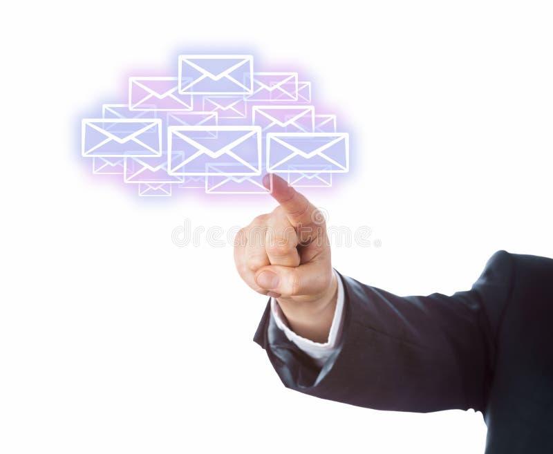 Arm som siktar på många Emailsymboler som bildar ett moln fotografering för bildbyråer