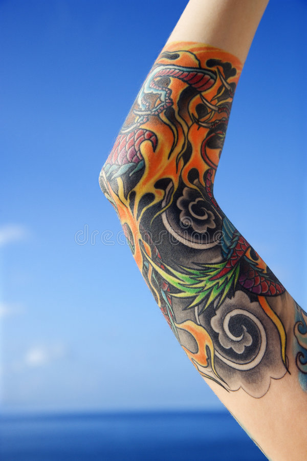 Arm of tattooed woman. Close up of tattooed woman's arm with Pacific Ocean in background in Maui, Hawaii, USA stock photography