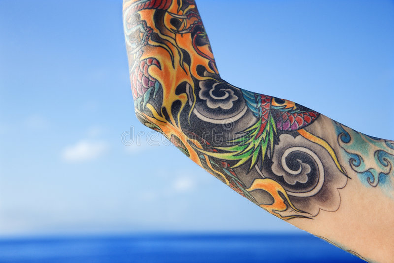 Arm of tattooed woman. Close up of tattooed woman's arm with Pacific Ocean in background in Maui, Hawaii, USA stock photos