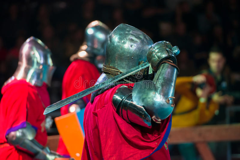 The arm to strike is entered. MOSCOW - DECEMBER 03, 2016: Armored fighters , dressed as knights, fighting at the XI World championship in Medieval combat CUP ` stock photography