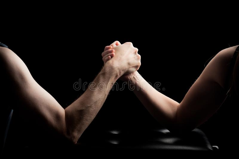 Arm wreslting man woman black background royalty free stock photography