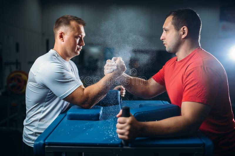 Arm wrestlers fighting, dust from talc in the air. Two arm wrestlers fighting on their hands at the table with pins, the dust from the talc in the air, wrestling royalty free stock photos