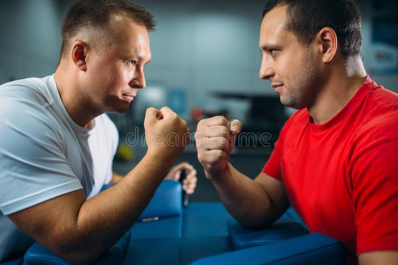 Arm wrestlers fighting, dust from talc in the air. Two arm wrestlers fighting on their hands at the table with pins, the dust from the talc in the air, wrestling stock image