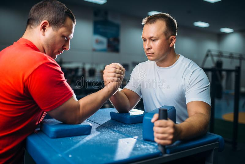 Arm wrestlers prepares for battle at the table. Two arm wrestlers prepares for the battle at the table with pins, workout before wrestling competition. Wrestle stock images