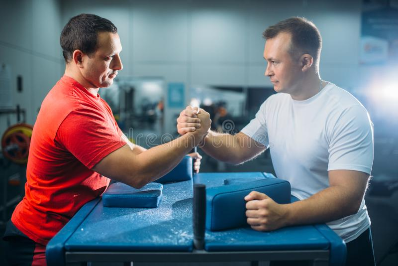Arm wrestlers prepares for battle at the table. Two arm wrestlers prepares for the battle at the table with pins, workout before wrestling competition. Wrestle stock photography