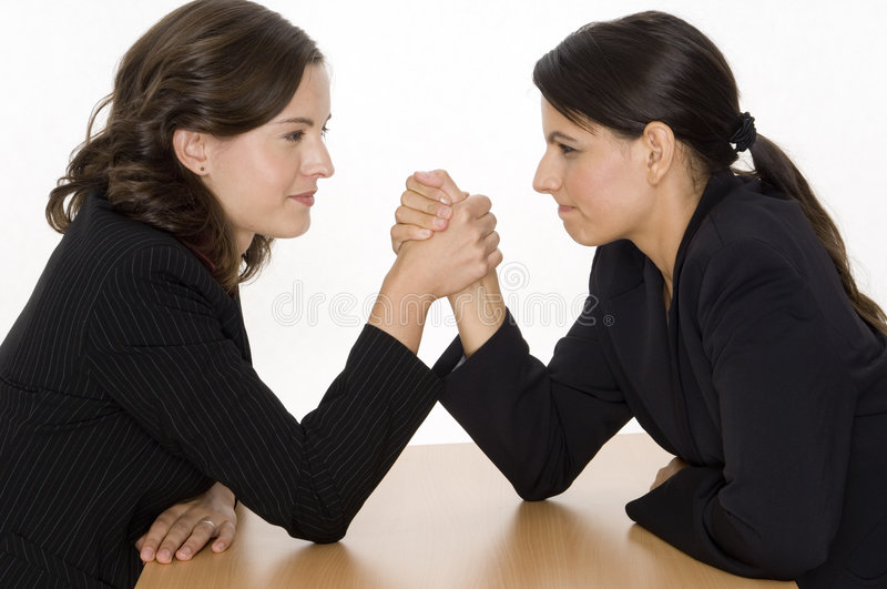 Arm Wrestling. Two women arm wrestling at work on desk on white background royalty free stock photography