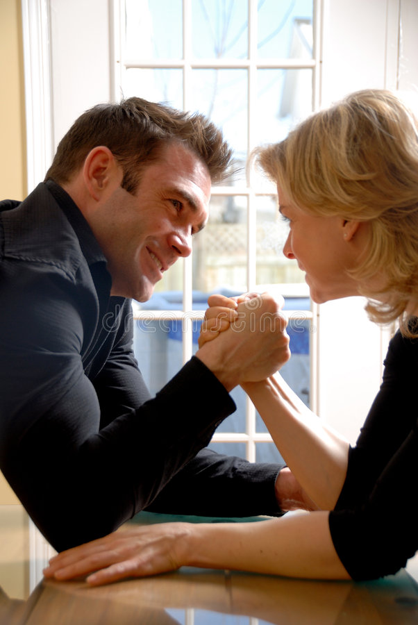 Arm wrestling. Angry couple battling it off with some arm wrestling royalty free stock photography
