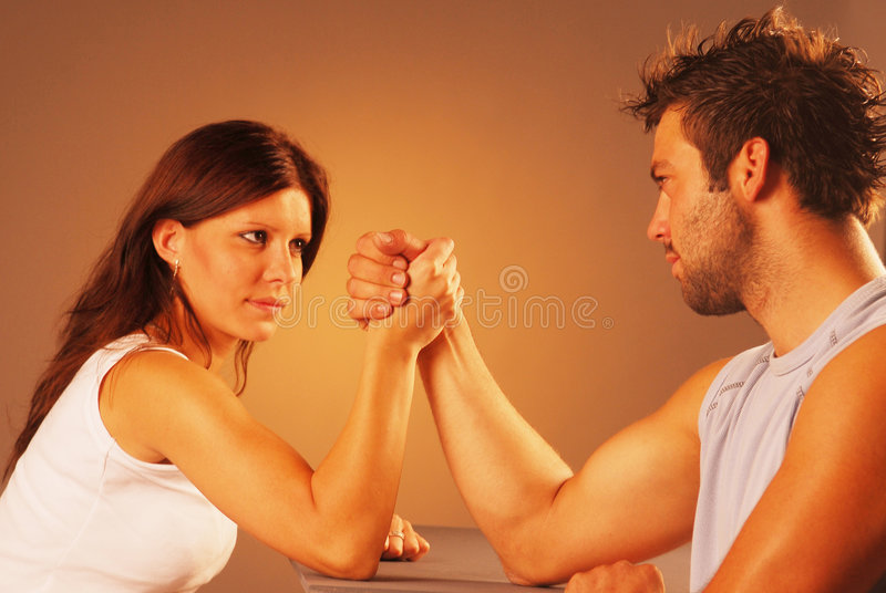 Arm wrestling. Between woman and man royalty free stock photo