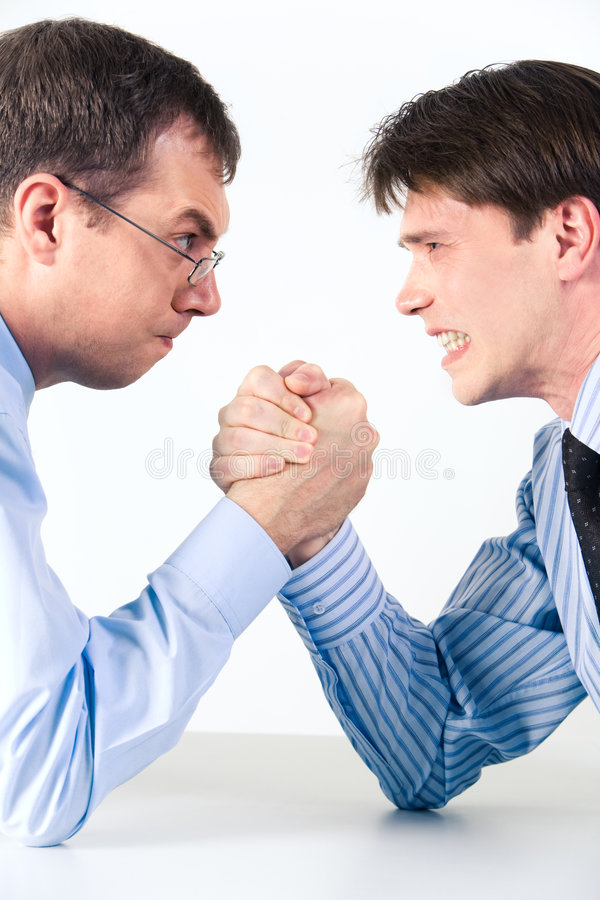 Arm wrestling. Conceptual photo of business competition: two businessmen wrestling with aggressive expression on their faces royalty free stock photos
