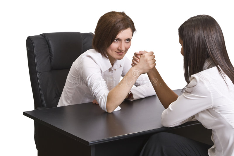 Arm wrestling. Businesswomen arm wrestling against a white background royalty free stock images