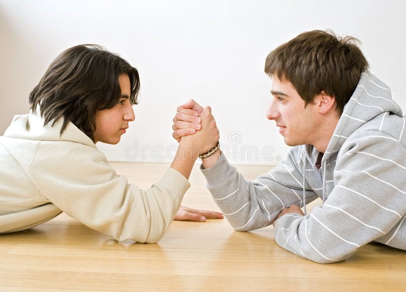 Arm wrestling. Two brothers arm wrestling on the floor stock photos