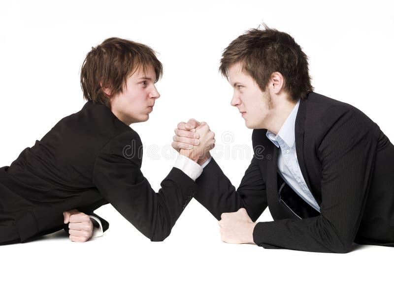Arm wrestling. Two men Arm wrestling towards white background stock photography