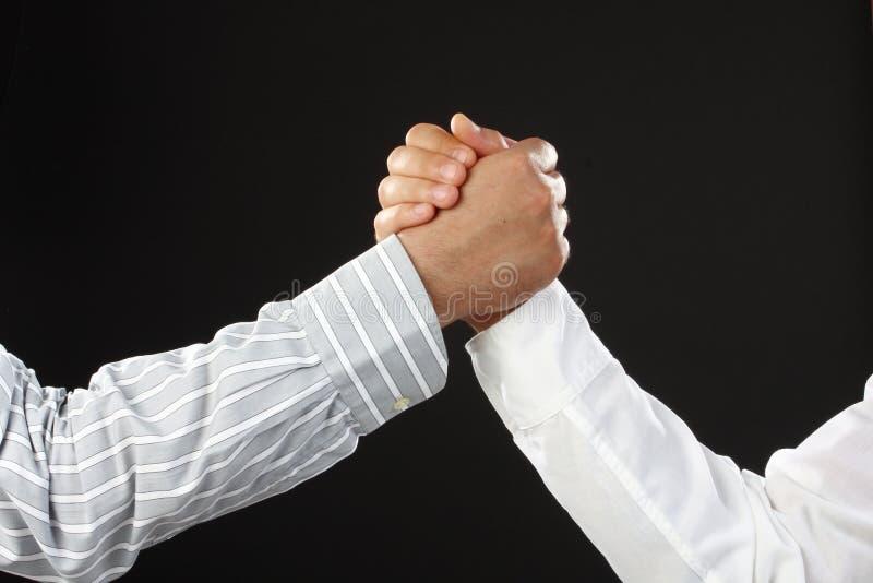 Arm wrestling business. Hands over black , arm wrestling business stock image