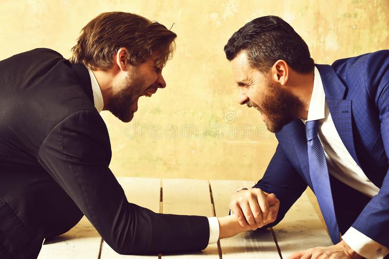 Arm wrestling of businessman and aggressively compete man. Co workers and dominance stock photo