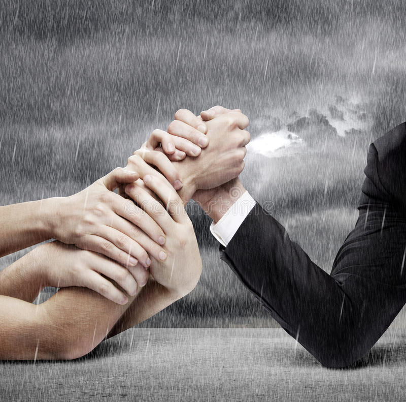 Arm wrestling. Businessman in opposition with many hands stock images