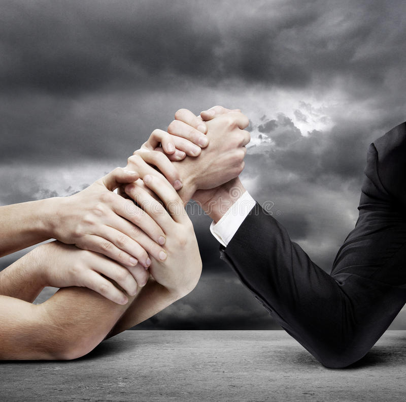 Arm wrestling. Businessman in opposition with many hands stock photo