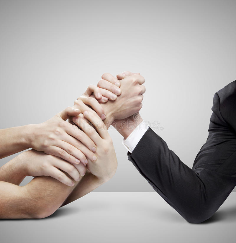 Arm wrestling. Businessman in opposition with many hands on gray background royalty free stock image