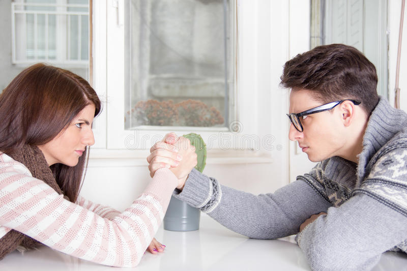 Arm wrestling challenge between a young couple royalty free stock photos
