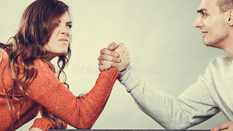 Arm wrestling challenge between young couple. Partnership relationship concept. Girlfriend confronts his boyfriend. Woman and men arm wrestling challenge between royalty free stock photo