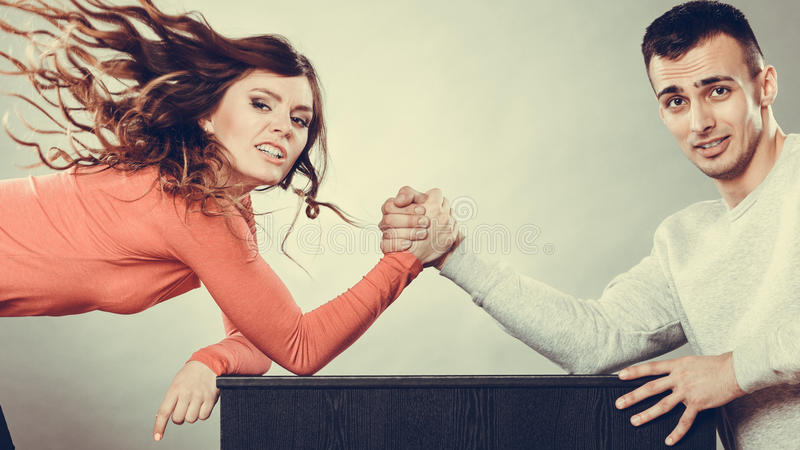 Arm wrestling challenge between young couple. Partnership relationship concept. Girlfriend confronts his boyfriend. Woman and men arm wrestling challenge between stock images