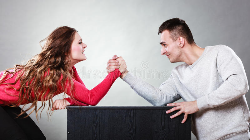 Arm wrestling challenge between young couple. Partnership relationship concept. Girlfriend confronts his boyfriend. Woman and men arm wrestling challenge between royalty free stock photography