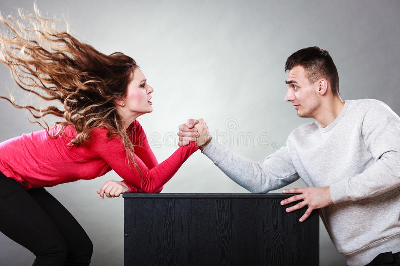 Arm wrestling challenge between young couple. Partnership relationship concept. Girlfriend confronts his boyfriend. Woman and men arm wrestling challenge between stock image