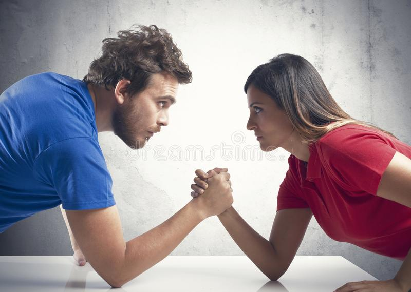 Arm wrestling between a couple. Arm wrestling challenge between a young couple royalty free stock photography
