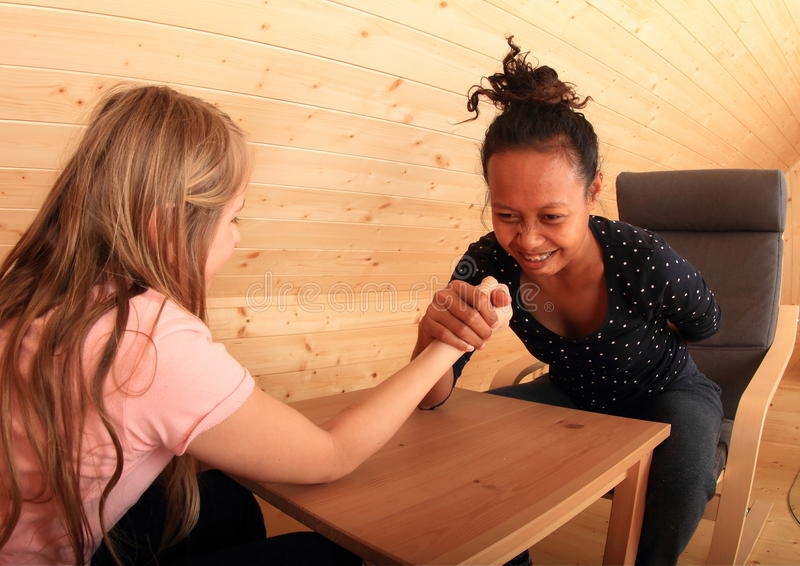 Arm wrestling - fighting girls. Girls trying arm wrestling - Caucasian kid and smiling young Papuan women fighting on wooden table in attic room stock photos