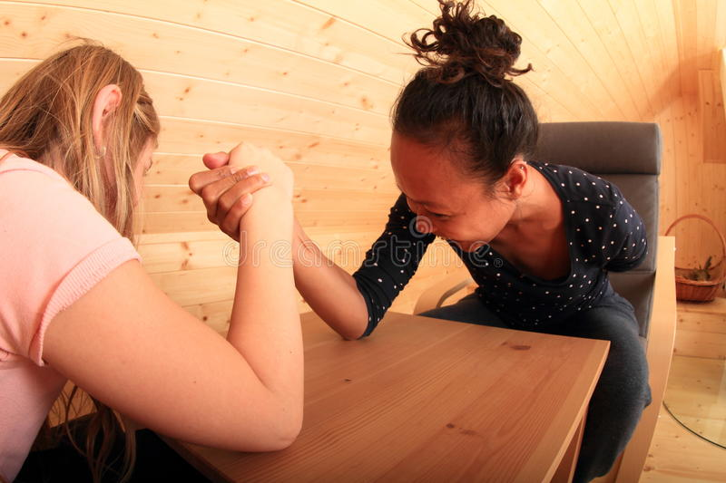 Arm wrestling - fighting girls. Girls trying arm wrestling - Caucasian kid and smiling young Papuan women fighting on wooden table in attic room stock image