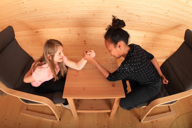 Arm wrestling - fighting girls. Girls trying arm wrestling - smiling Caucasian kid and young Papuan women fighting on wooden table in attic room stock photos