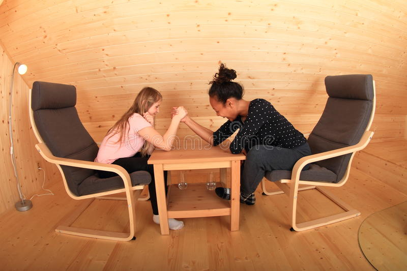 Arm wrestling. Girls trying arm wrestling - smiling Caucasian kid and young Papuan women sitting in armchairs in wooden attic room stock photo